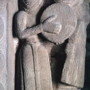 Capitel do presbiterio da igrexa de San Xuan d'Amandi (Villaviciosa, Asturies, s. XIII) no que se aprecia unha dona tocando un pandeiro redondo.  Fotografía de Ignacio Acuña, colección do Muséu del Pueblu d'Asturies.