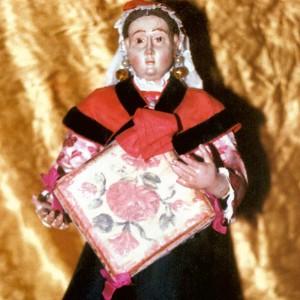 Figuriña que representa unha tocadora de pandeiro cadrado no nacemento das Agustinas de Vilagarcía de Arousa (Pontevedra, s. XVIII). Obsérvese a decoración da pel, o predominio dos tons encarnados fundamentalmente arredor do marco, os lazos e a posición no que a muller terma del. Do arquivo de Ramón Marín.