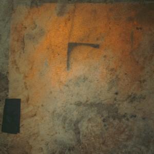 Detalle a contraluz do pandeiro de María Grande Sobral (Cortellas, Soutomaior, Pontevedra) (35.7 cm de lado, 4.5 cm de grosor) amosando unha peza de madeira en forma de ángulo que se acha no seu interior pegada a ambas peles para impedir a súa resonancia. Fotografía do autor.