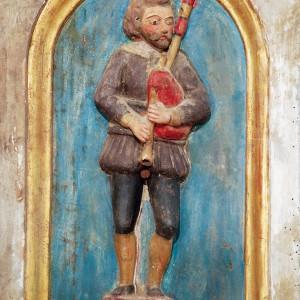 Gaiteiro representado no banco do retábulo de Santa María de Meiraos (1614, Folgoso do Courel, Lugo). Este músico está acompañado no mesmo banco por un tocador de frauta e tambor. Fotografía do autor.