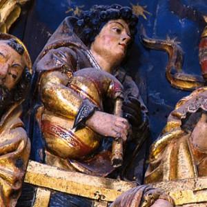 Gaiteiro representado na adoración do neno do que fora retablo maior da catedral de Lugo, obra de Cornelis de Holanda do 1534. Obsérvese  que a gaita de fol non ten roncón e o vestido do fol está ricamente  ornamentado. Ao lado dereito, sobre o ombreiro doutro pastor, asoma  o que podería ser o roncón doutra gaita de fol. Fotografía do autor.