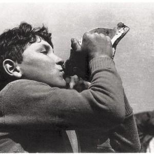 Rapaz tocando a buguina. Fotografía tirada da publicación de Gonzalo Allegue Galicia. O oficio de vivir. O Mar. Ed. Nigra S.L.