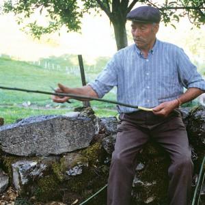 Indalecio Rodríguez Ares (Vilariño de Conso, Ourense) fabricando unha gaita de castiñeiro; extraendo a codia dunha póla para facer o bordón. Fotografía do autor.
