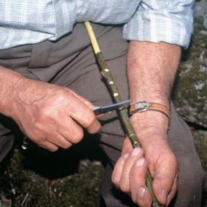 Indalecio Rodríguez Ares (Vilariño de Conso, Ourense) fabricando unha gaita de castiñeiro; facendo os furados no tubo melódico antes de extraer a codia. Fotografía do autor.