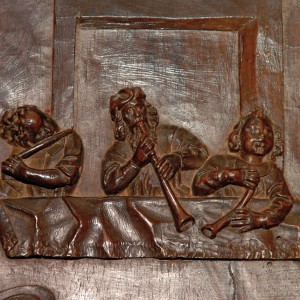 Conxunto de frauta traveseira (esquerda), óboe (centro) e corneta (dereita) no cadeirado do coro de San Martiño Pinario (Santiago de Compostela, s. XVII). Fotografía do autor.